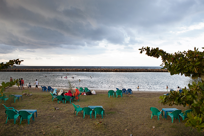 Women sitting by a seawall in Banda Aceh, Indonesia.